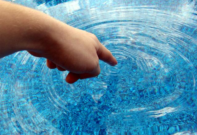 ruka, která ukazuje prsem na hladinu vody a dotýká se jí